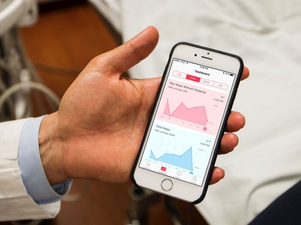 A doctor holding an iPhone open to the Vasctrac App