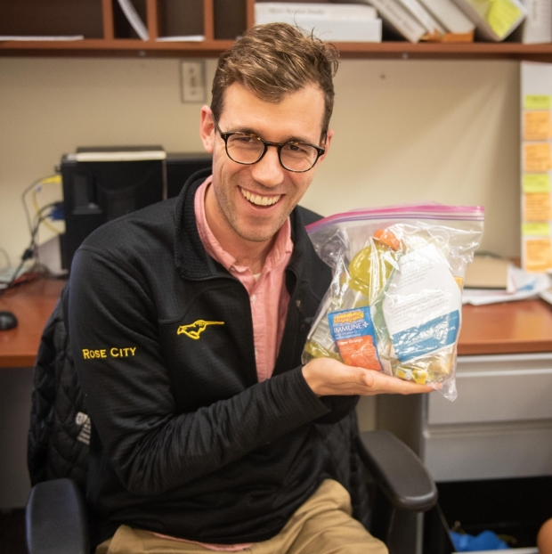 General Surgery Resident Ken Perrone holds up a surgical babushka care package.