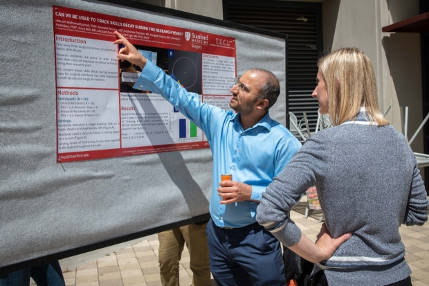 Dr. Hossein Mohamdipanah explains his scientific poster to new faculty member Carolyn Sieb at Holman Day.